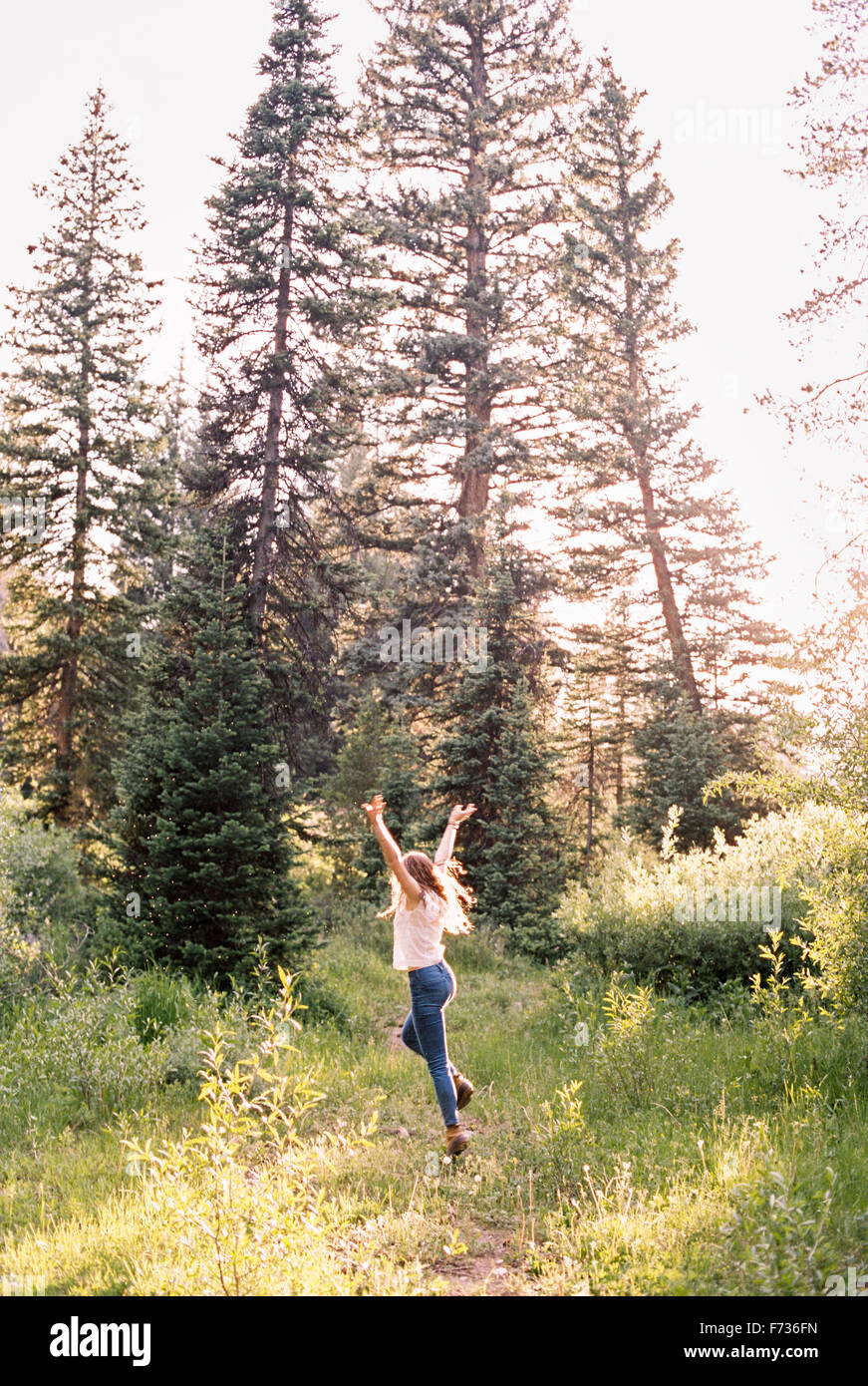 Woman jumping with joy in a sunlit forest. - Stock Image