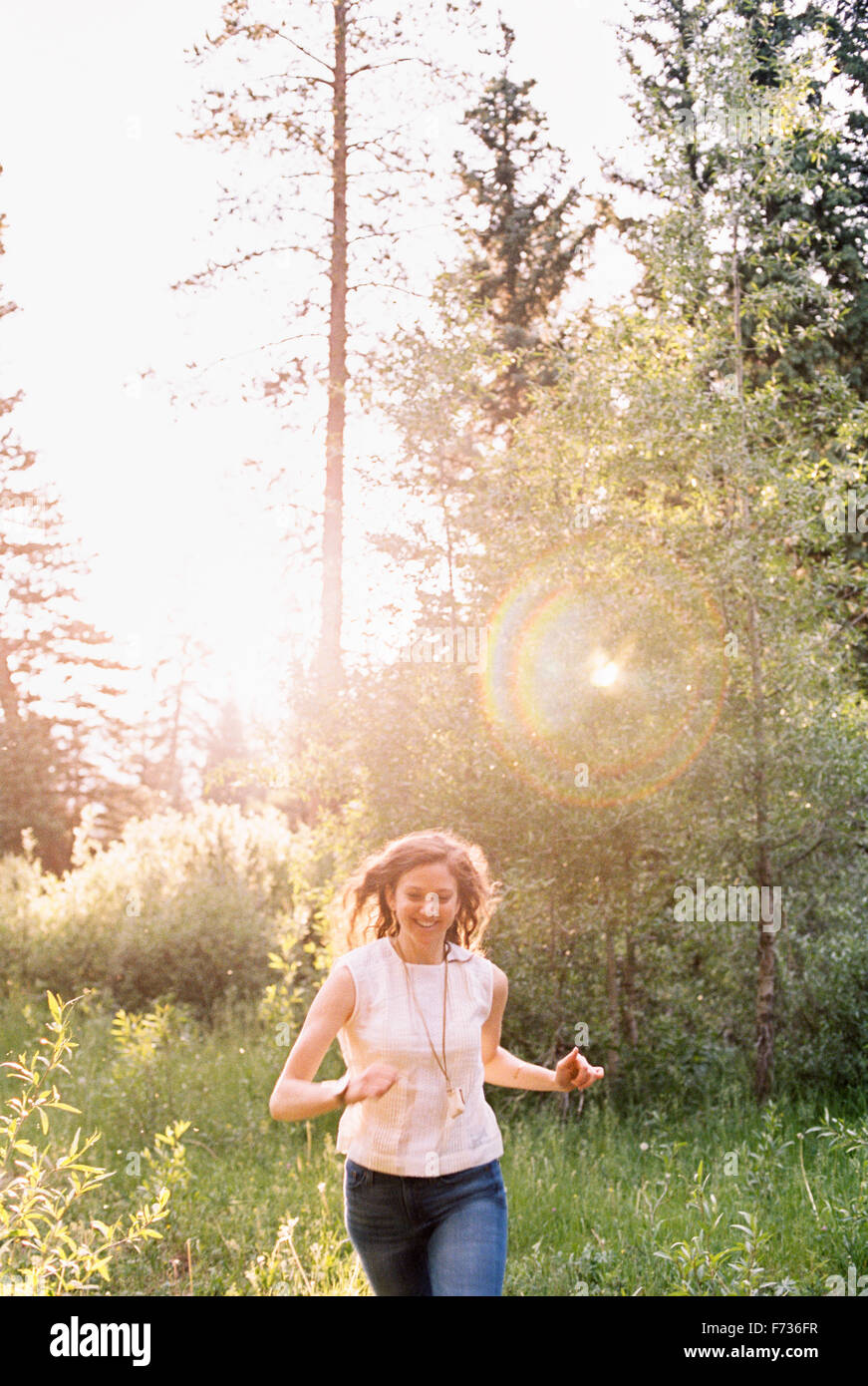 Smiling woman running through a sunlit forest. - Stock Image