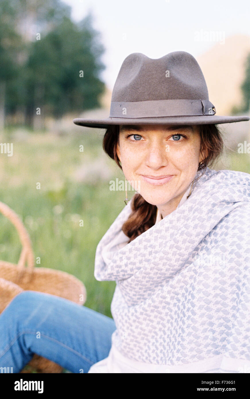 A woman in a hat and woollen shawl sitting in a meadow. - Stock Image