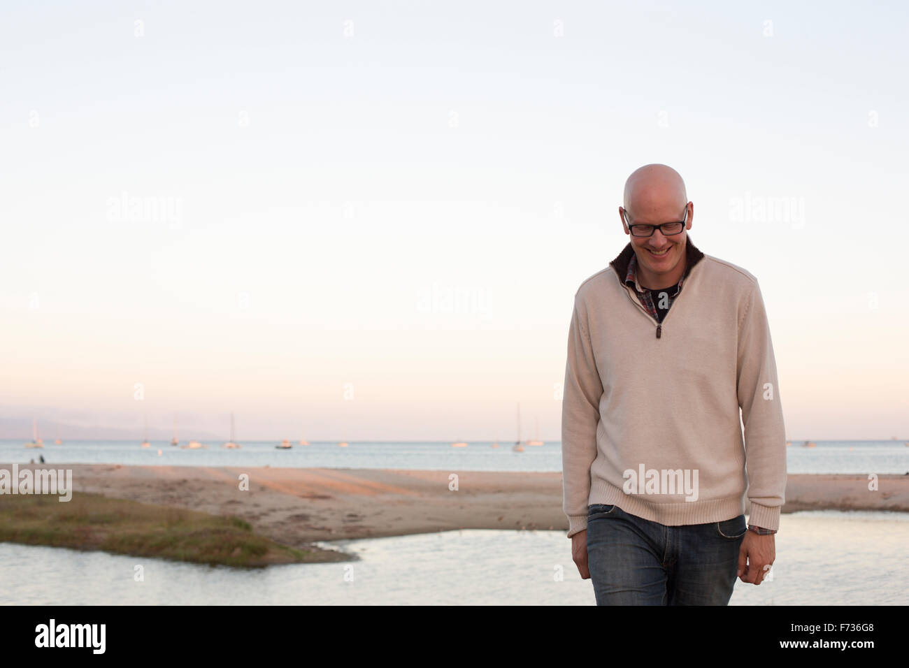 Bald man walking on a sandy beach by the ocean. - Stock Image