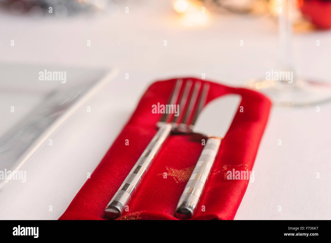 Table laid for Christmas dinner, decorated with baubles and tinsel and fairy lights. Knife fork and red napkin. - Stock Image