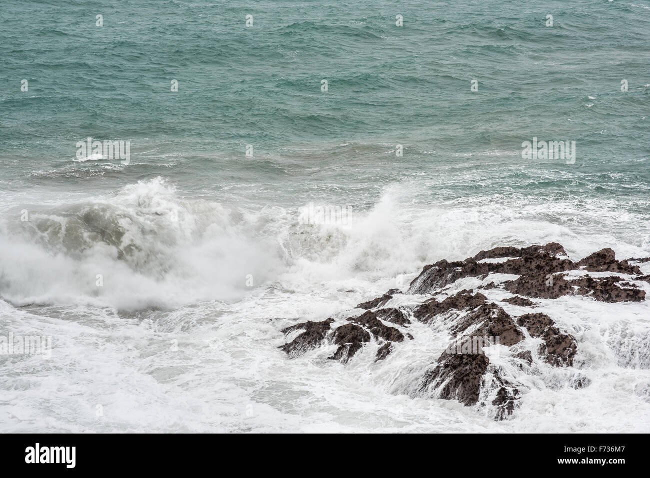 Spray bounces off rocks along the shoreline at Newquay, Cornwall, England. - Stock Image