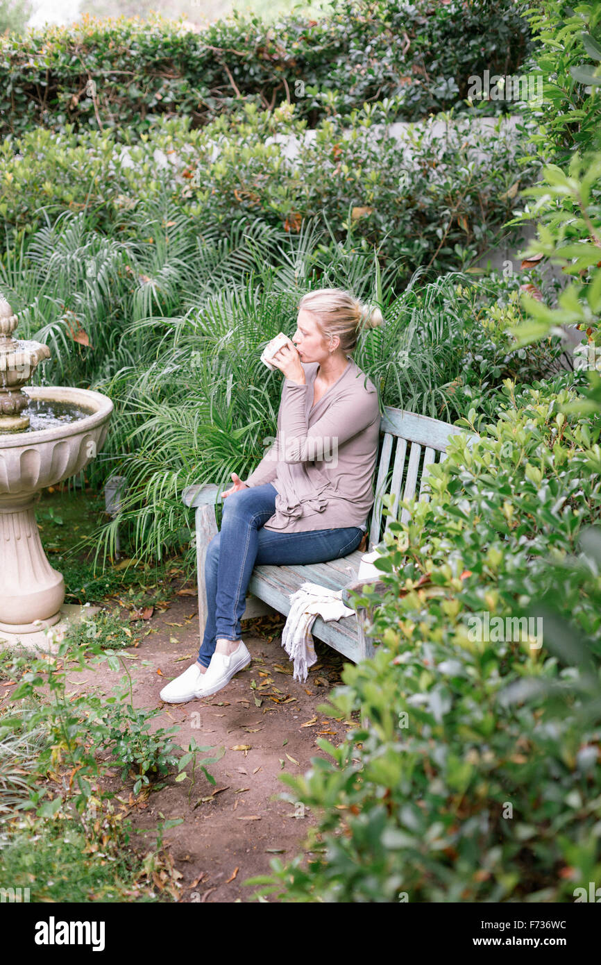 Woman sitting on a wooden bench in a garden, taking a break. - Stock Image