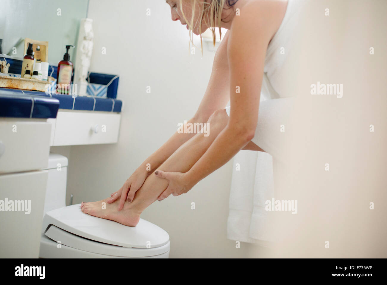 Woman wrapped in a white towel standing in a bathroom, applying lotion to her leg. - Stock Image