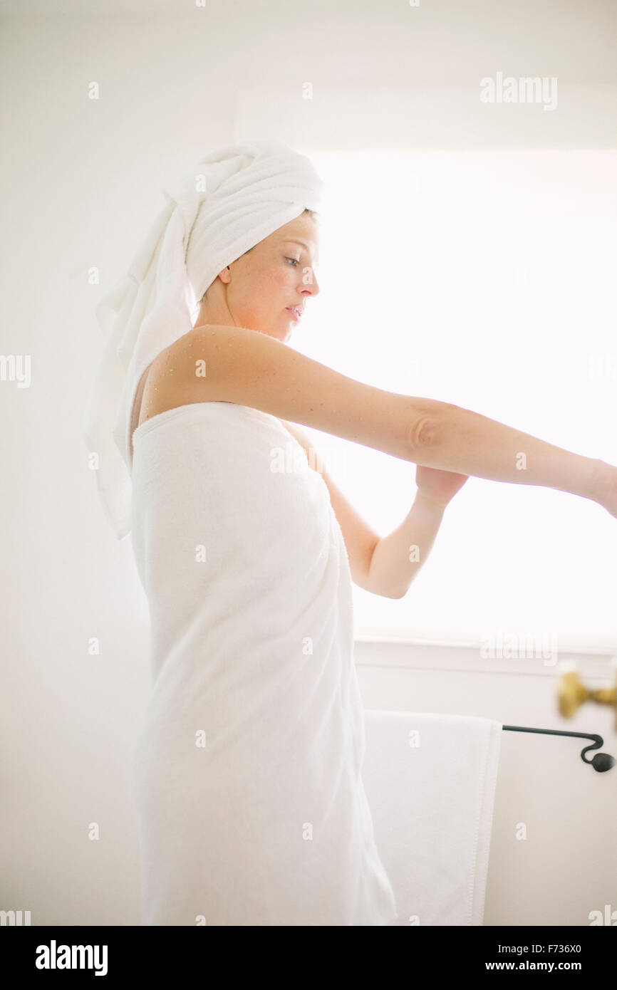 Woman wrapped in a white towel standing in a bathroom, applying lotion to her arm. - Stock Image