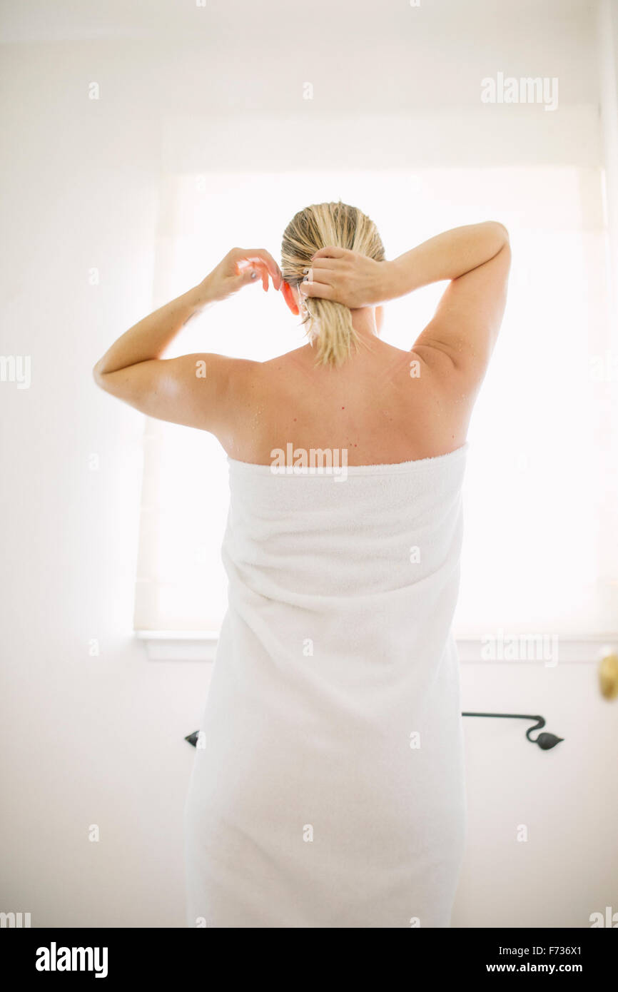 Woman wrapped in a white towel standing in a bathroom, tying her wet hair. - Stock Image