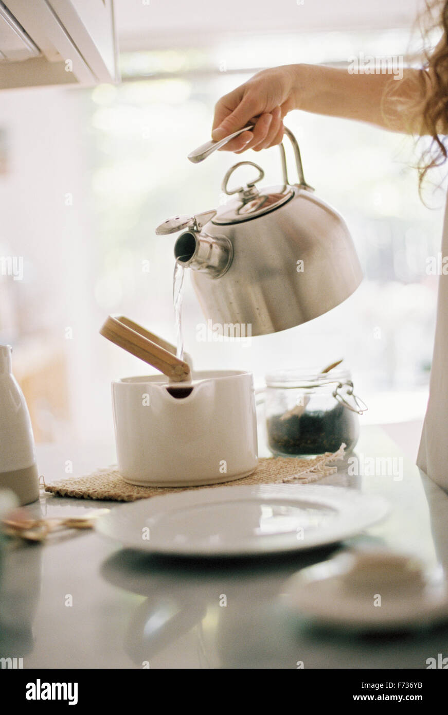 Woman standing in a kitchen pouring hot water from a kettle into a tea pot. - Stock Image