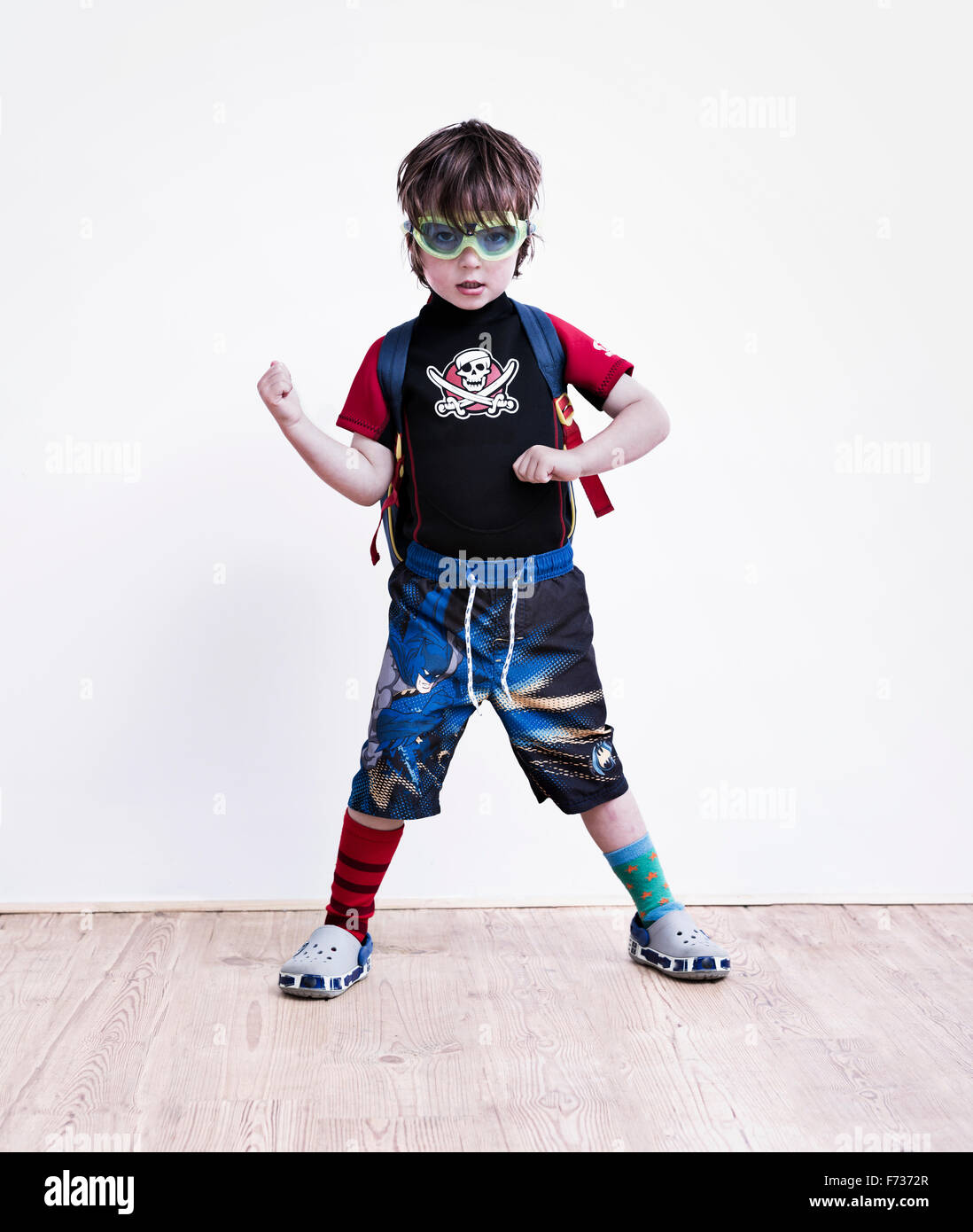 A boy standing with his legs apart posing in fancy dress, wearing a pirate tee-shirt, eye goggles and long shorts. - Stock Image