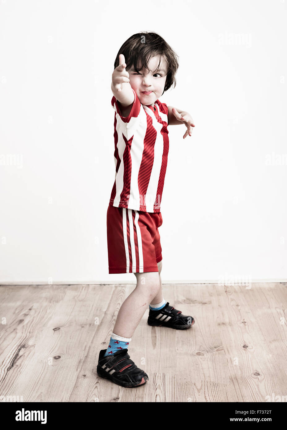 A boy in red and white striped shirt and football shorts standing pointing at the camera. Stock Photo