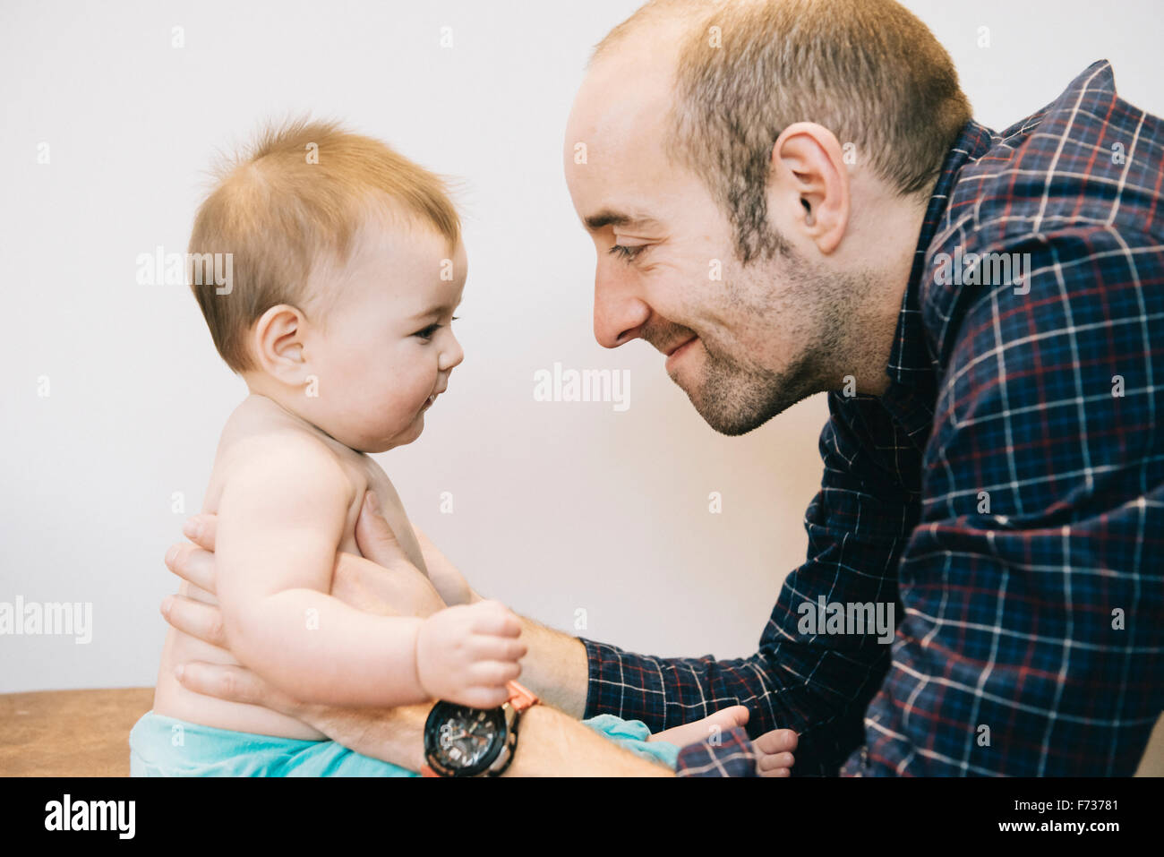 A young baby girl and her father face to face playing. - Stock Image