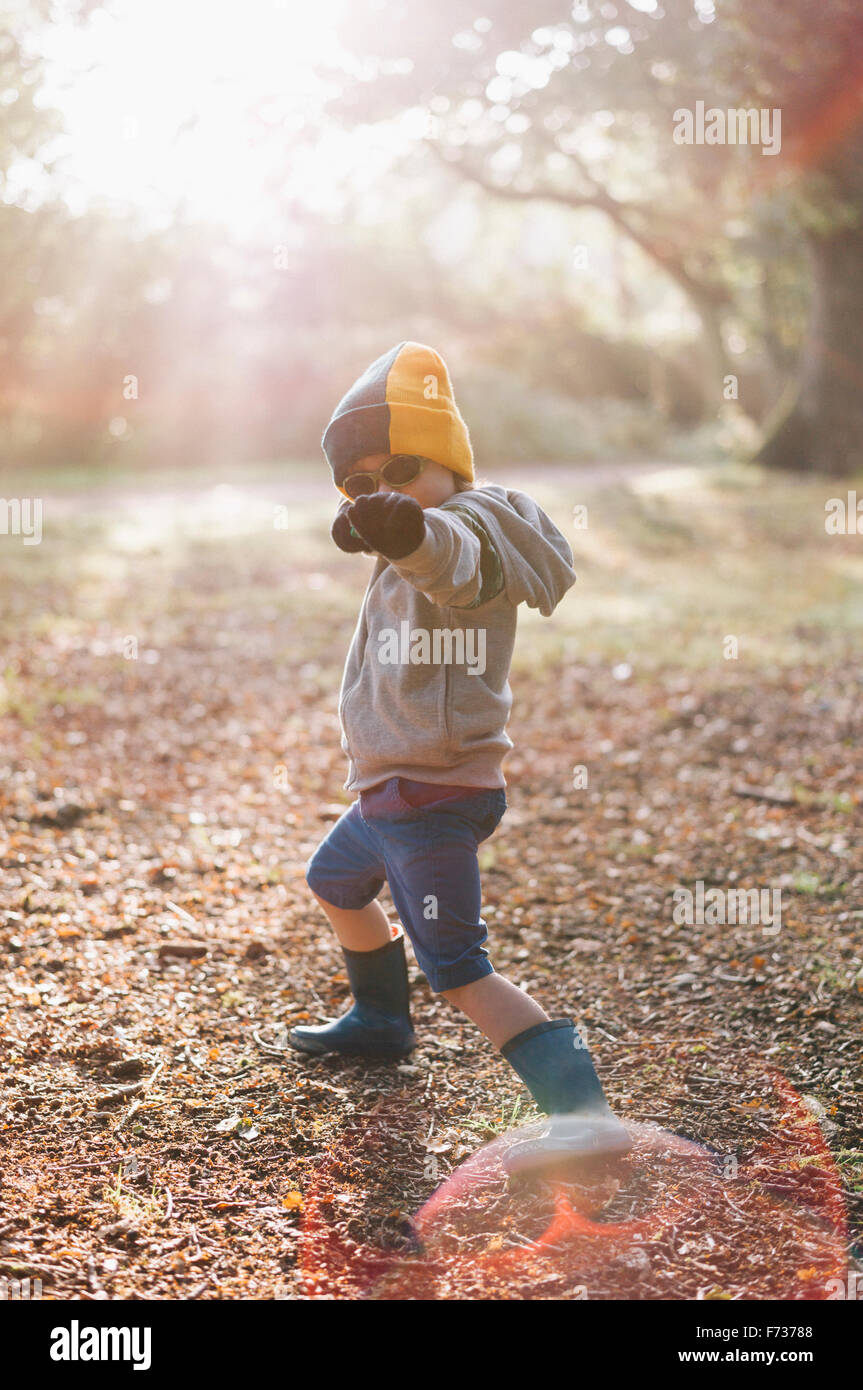 A boy outdoors in a woolly hat wearing shorts and wellington boots, striking a pose with an outstretched arm. - Stock Image