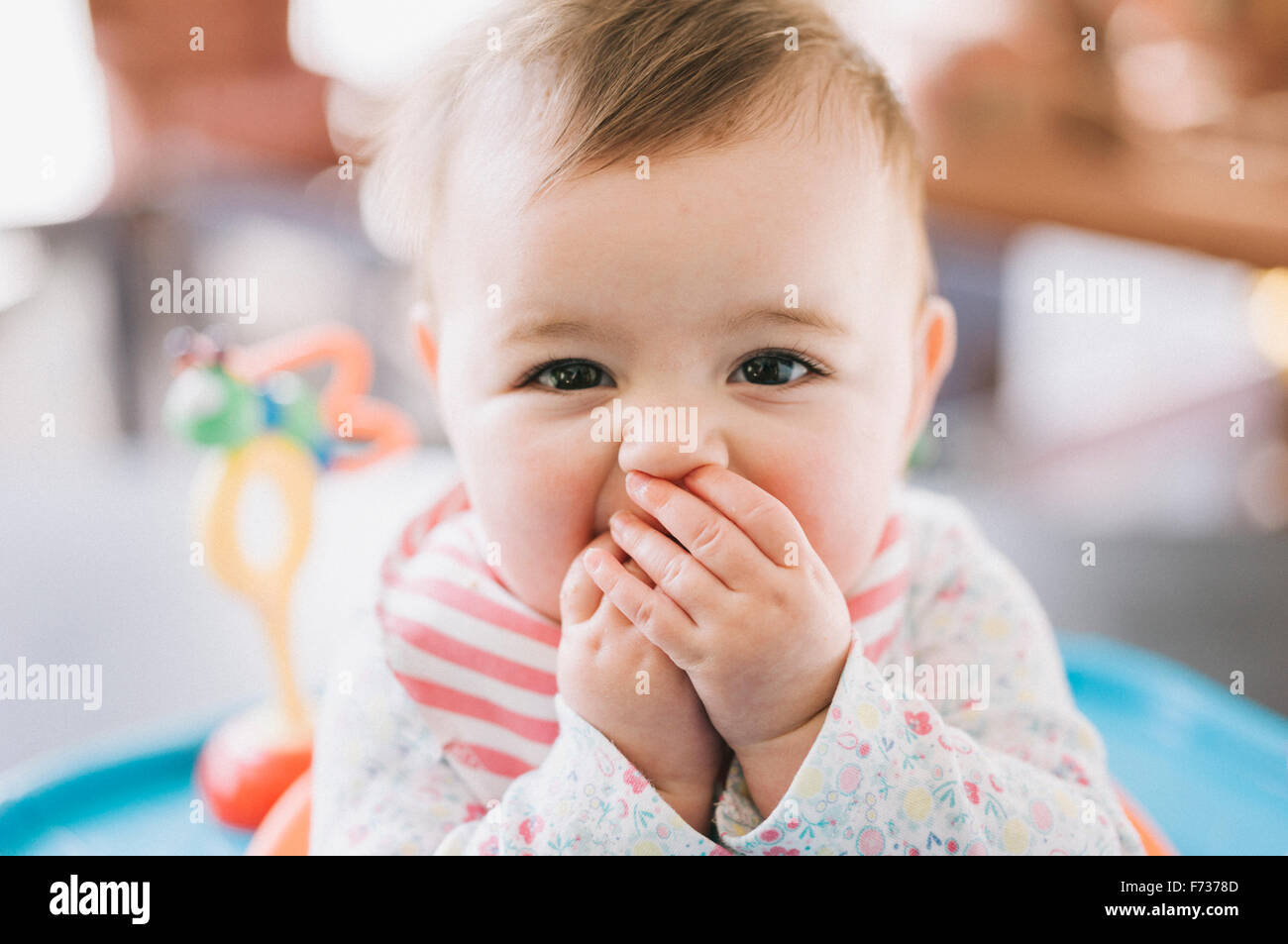 A baby girl with her hands covering her mouth, looking at the camera. - Stock Image