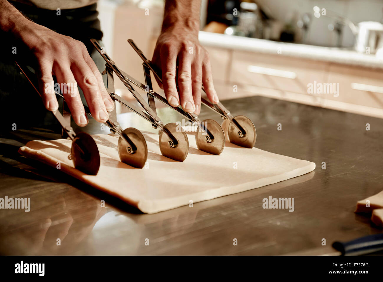 A baker working on a floured surface, dividing the prepared dough into squares using an expandable rotary dough - Stock Image