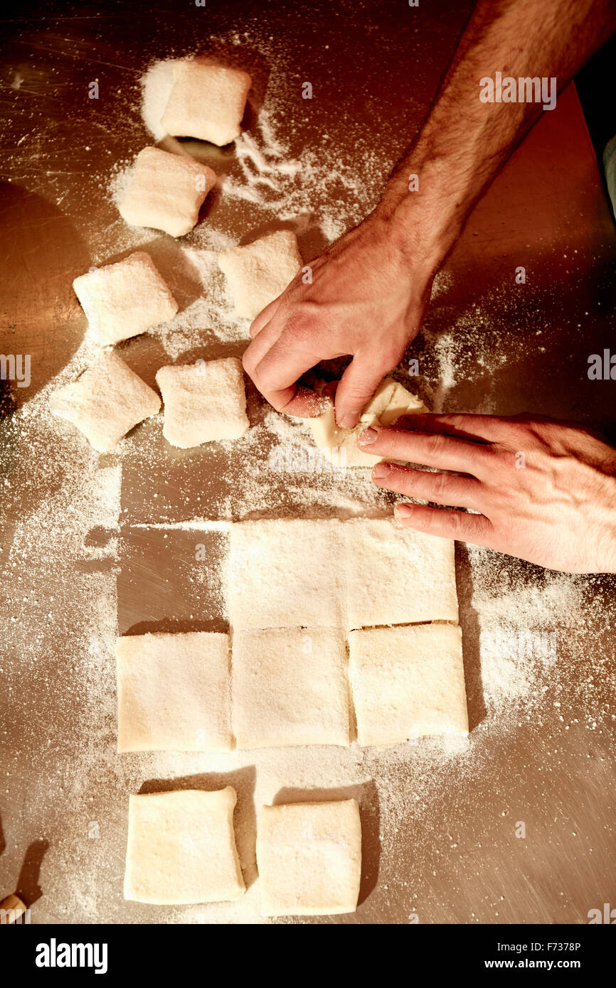 A baker working on a floured surface, dividing the prepared dough into squares. - Stock Image