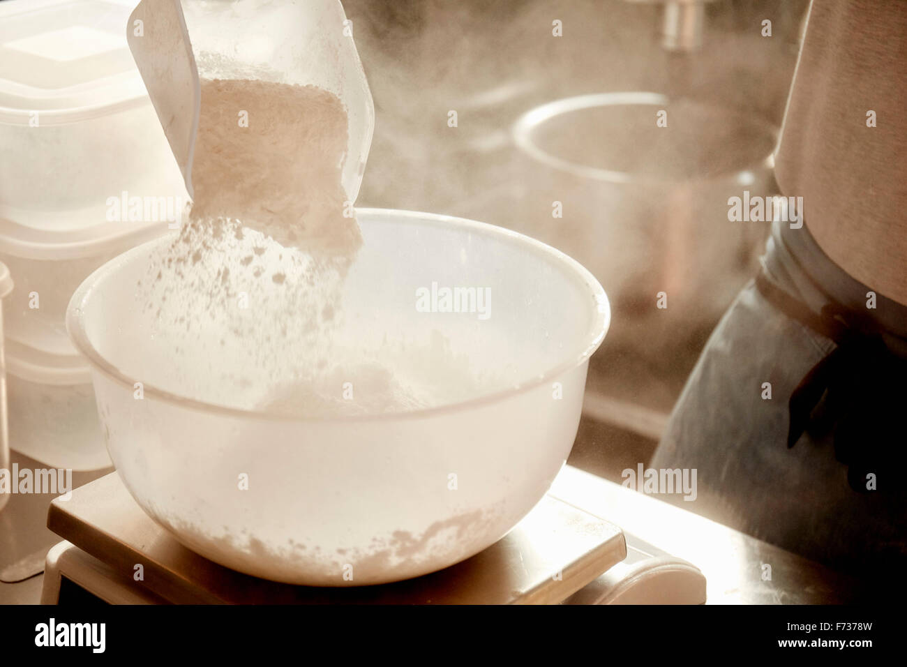 A baker preparing ingredients, using a measuring scale and pouring flour into a bowl. - Stock Image