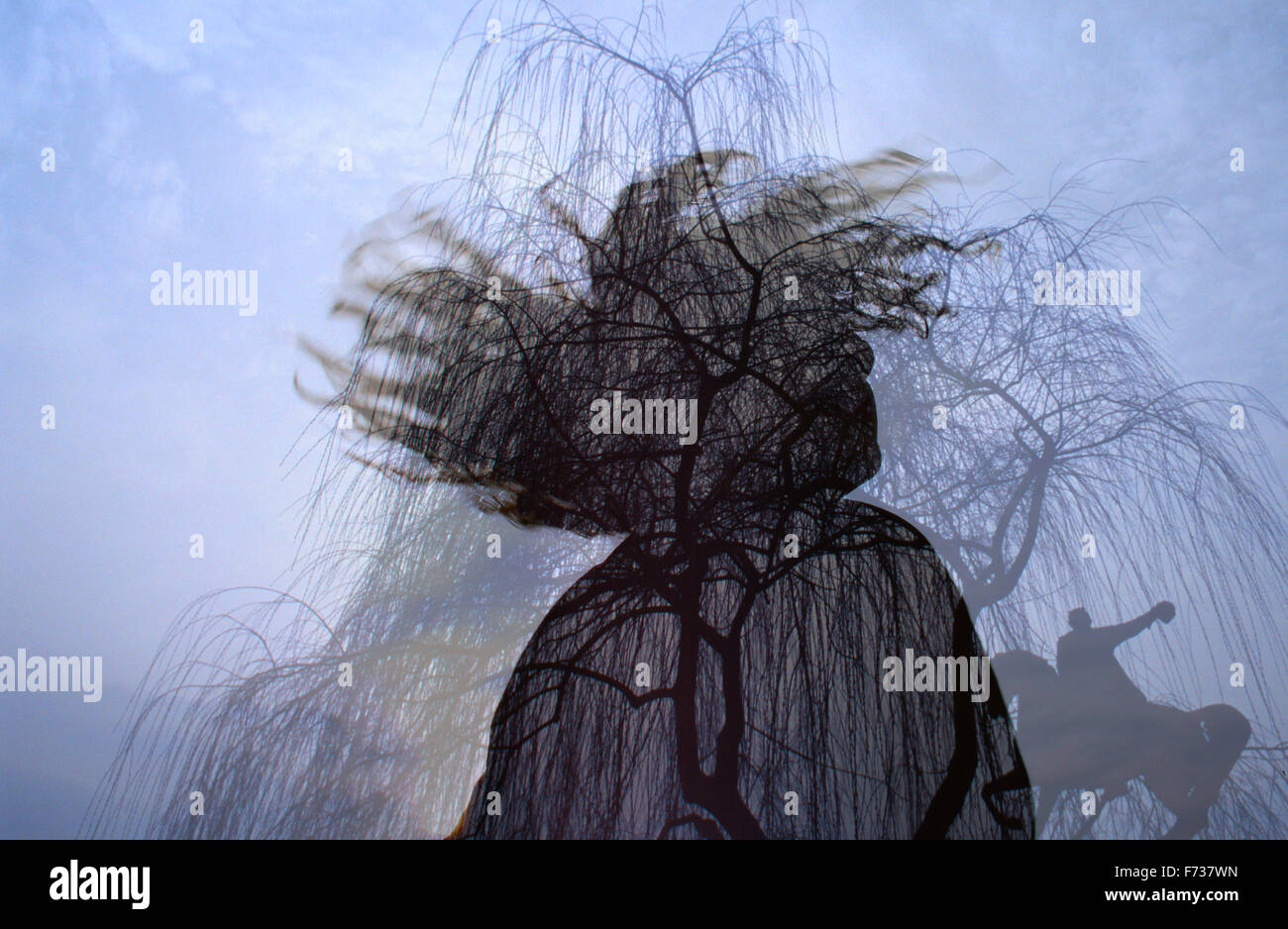 Double exposure of a young man twirling and tossing his hair with silhouette of an equestrian statue under leafless - Stock Image