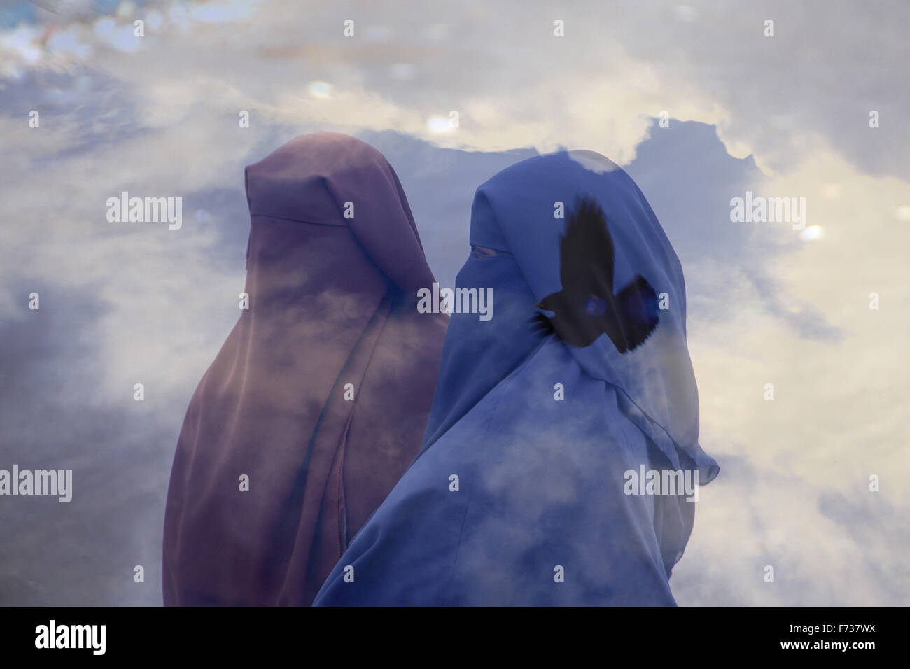 Double exposure of Muslim women wearing full Niqab veil and a bird flying in the sky - Stock Image