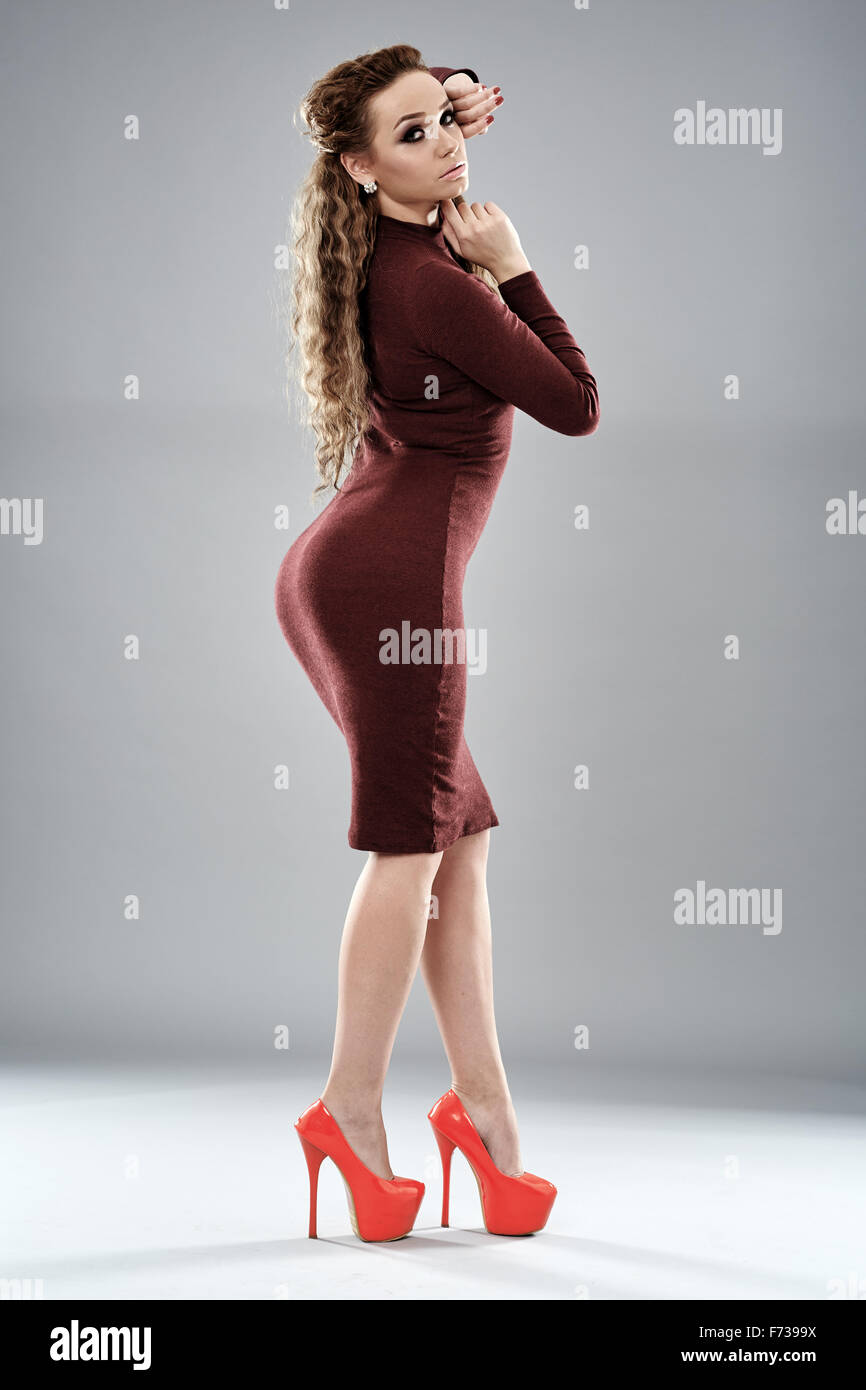 2e473f1639f Gorgeous fashion model in tight dress and high heels posing on gray  background