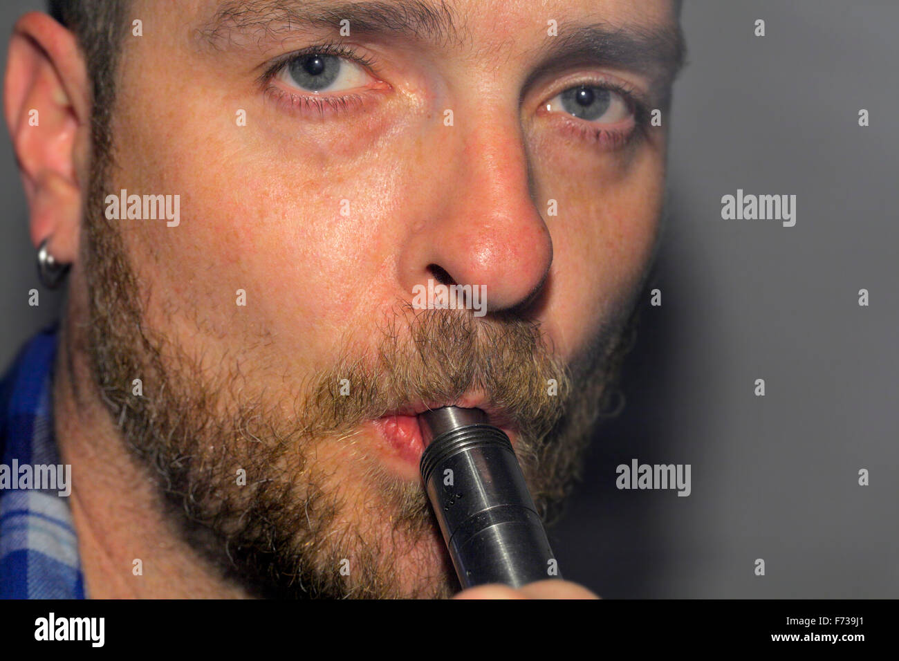 Man inhaling from a large e-cigarette. - Stock Image