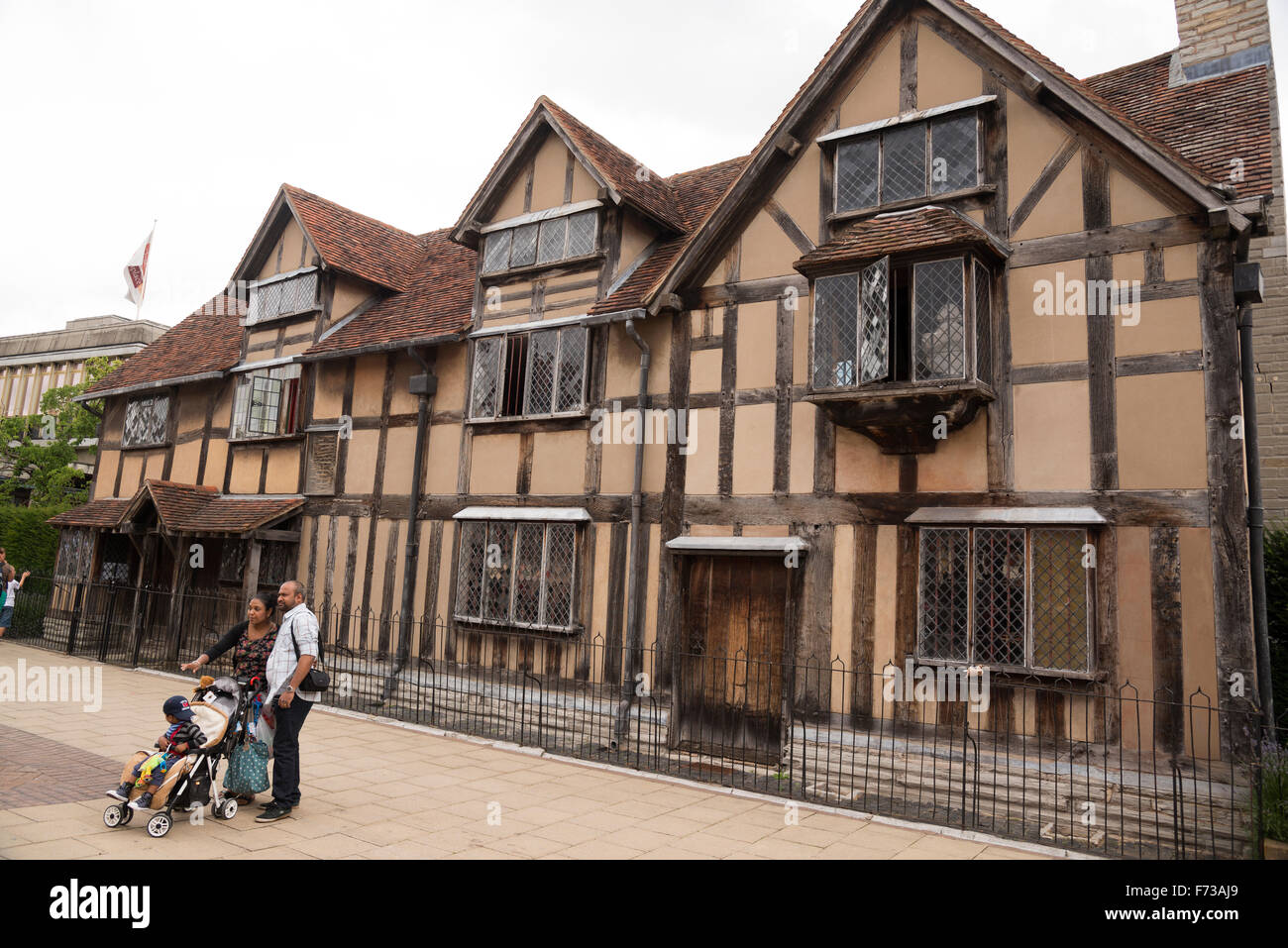 An ethnic family pose in front of a Shakespearean house in stratford-upon-avon - Stock Image
