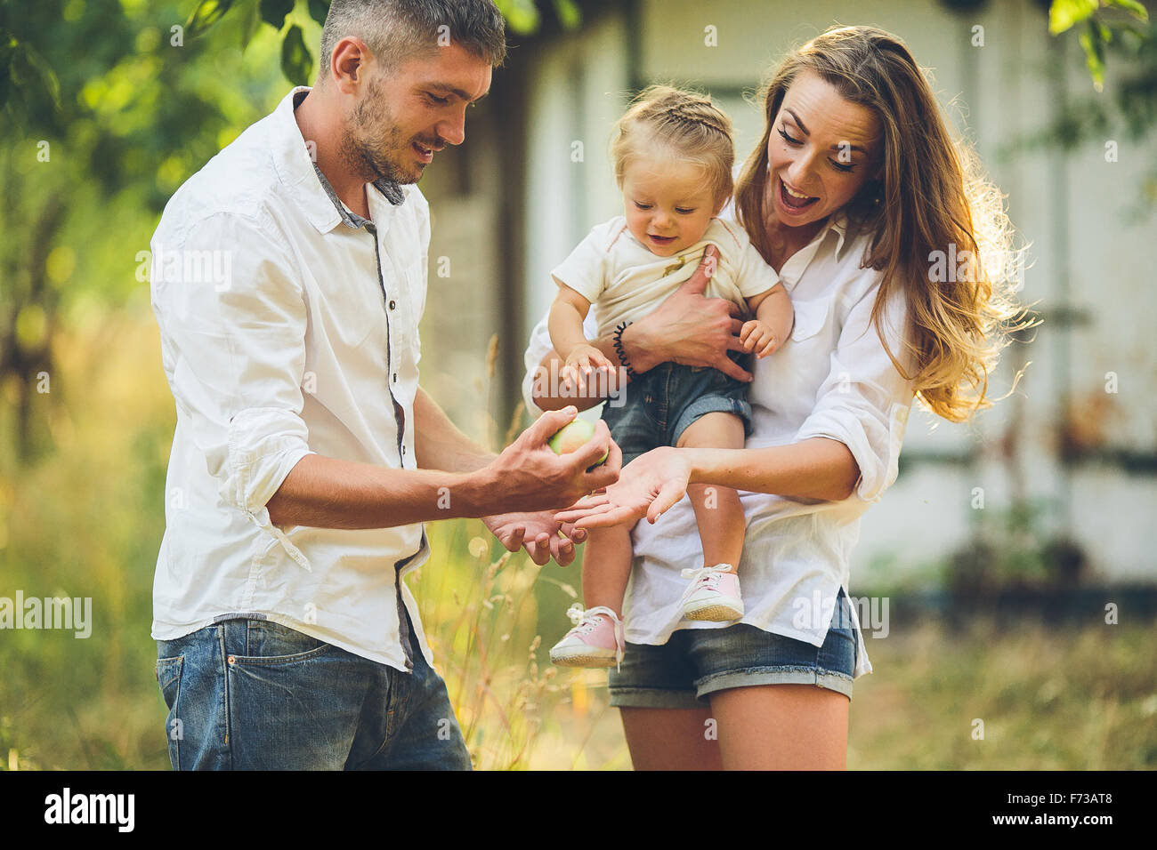 Families with a child in the summer garden - Stock Image