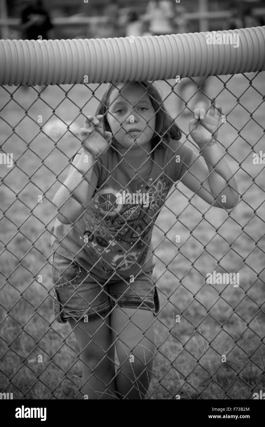 Lonely girl behind fence - Stock Image