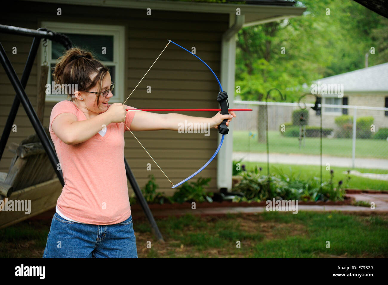 Pre-teen girl with bow and arrow in back yard - Stock Image