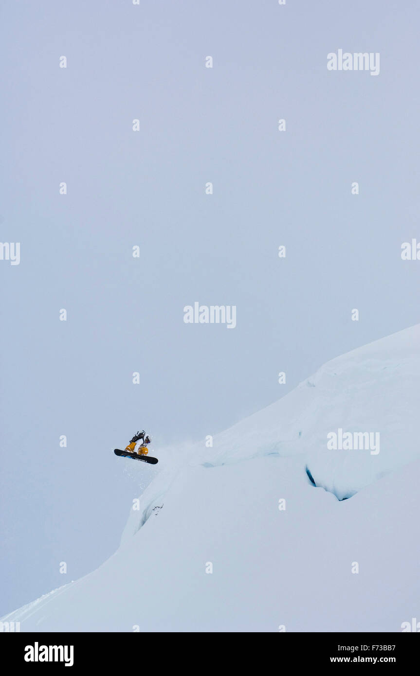 Shayne Pospisil spins off of a cliff in Valdez, Alaska. - Stock Image