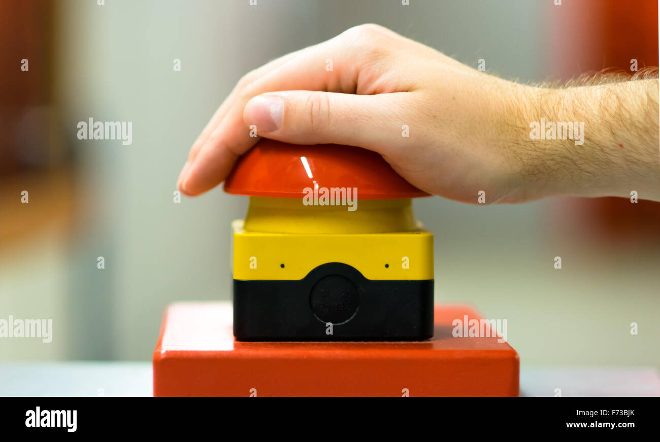 Hand pressing red buzzer - Stock Image