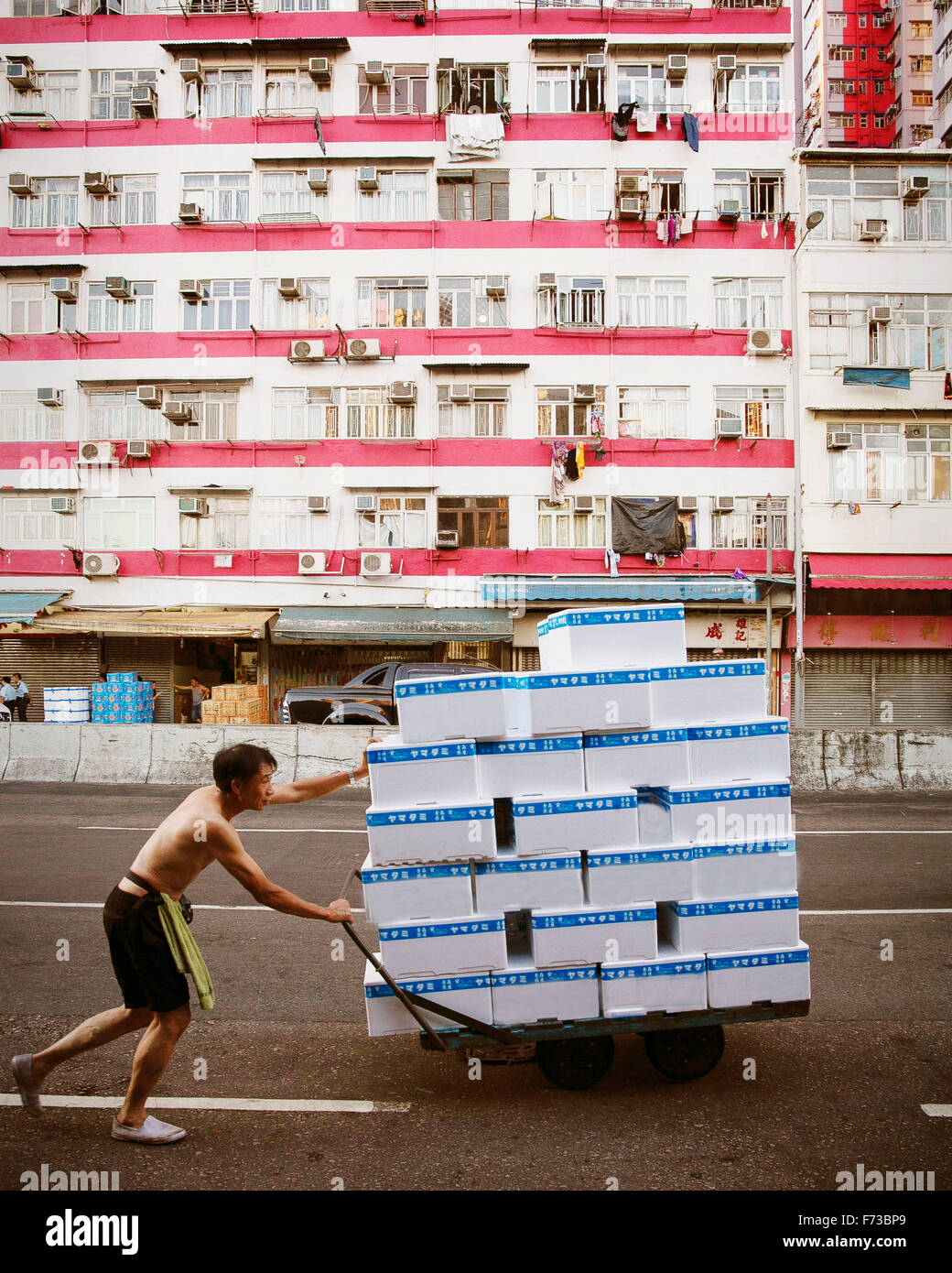 A person pushes a hand trolley loaded with white colour boxes along the road in Kowloon, Hong Kong on his left side Stock Photo