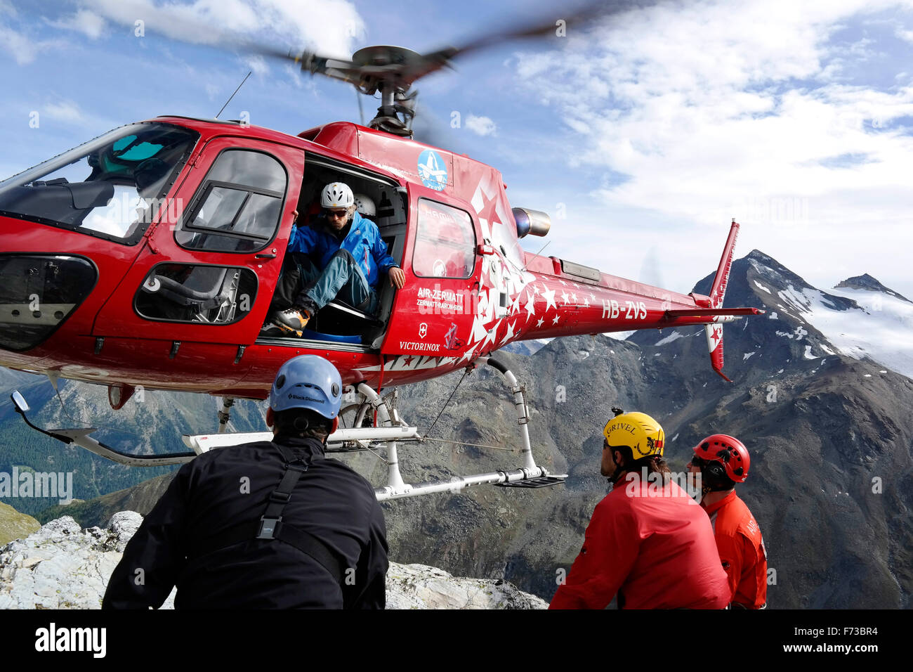 Mountain rescuers are landing with a Air Zermatt helicopter in the Swiss Alps. As the rotor blades are very close - Stock Image