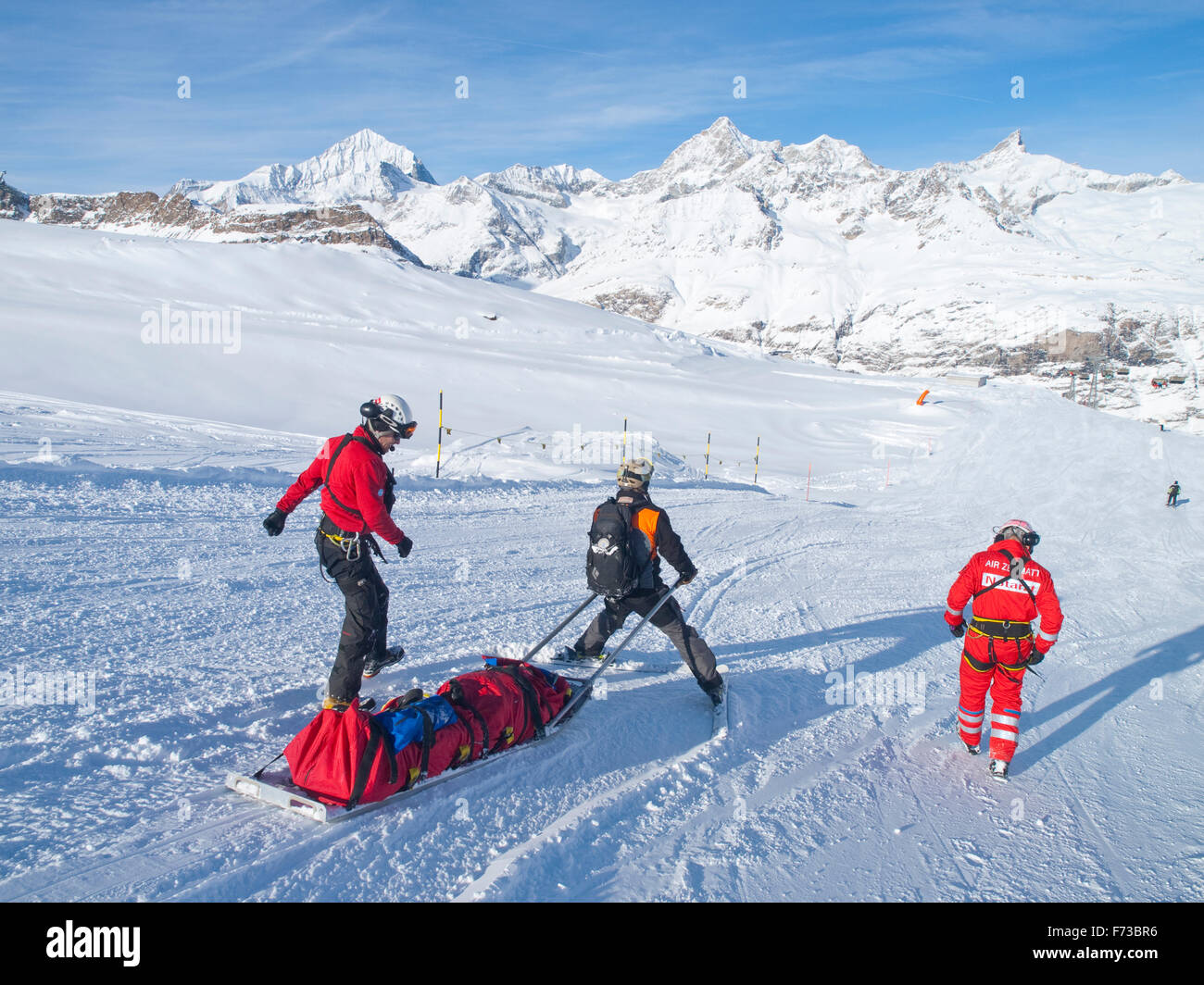 A rescue team is transporting a wounded skier on a rescue sled down the ski slope of ski resort Zermatt in the Swiss - Stock Image