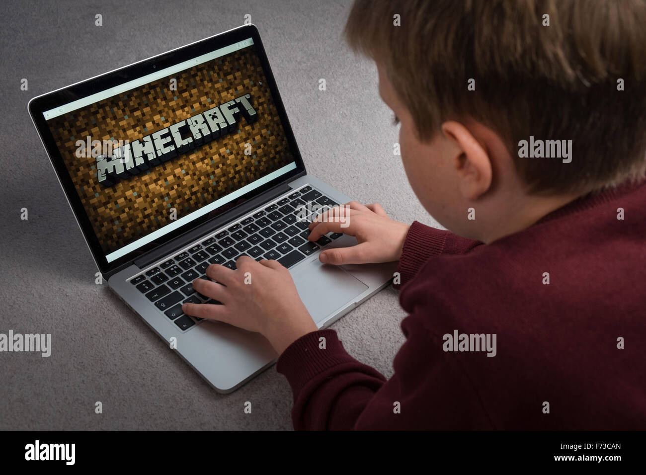 A child playing the Minecraft computer game on a laptop - Stock Image