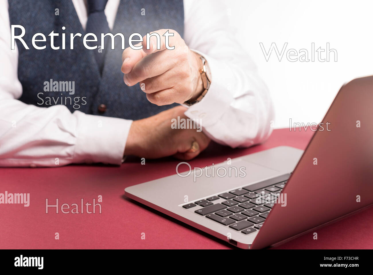 office situation with businessman sitting at desk pointing at the word retirement on a clear screen - Stock Image
