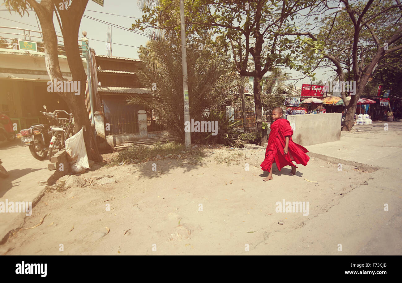 A young monk walks toward the school monks in Myanmar - Stock Image