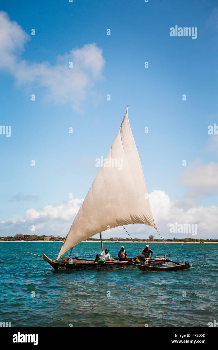 LAMU, KENYA, AFRICA. Three men sail a small dhow sailboat in turwuoise waters with beach in distance. - Stock Image