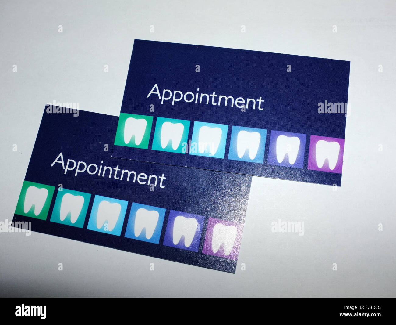 Two dentist appointments cards photographed against a white background. - Stock Image