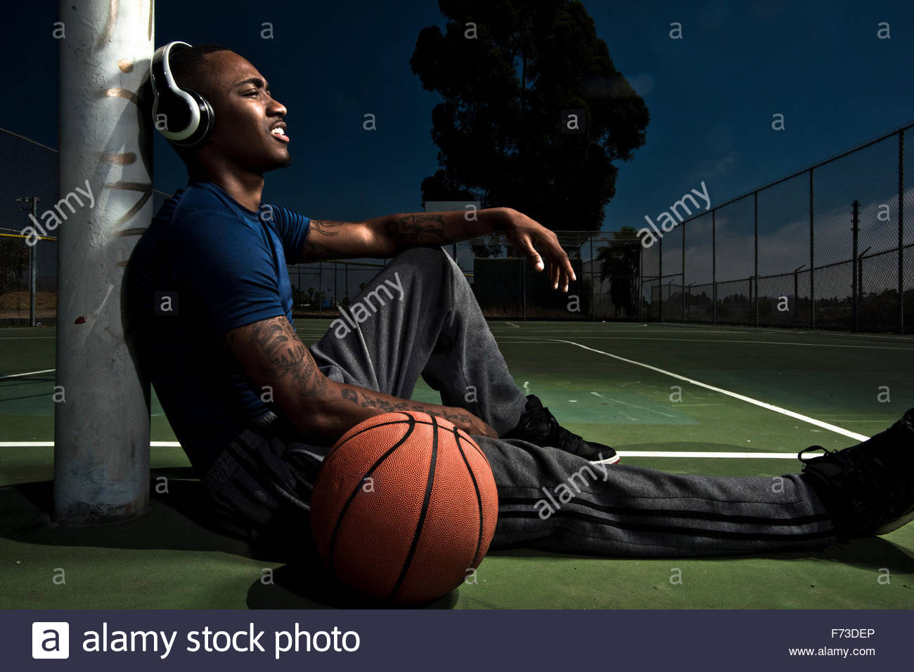 A basketball player listens to music before a game. - Stock Image