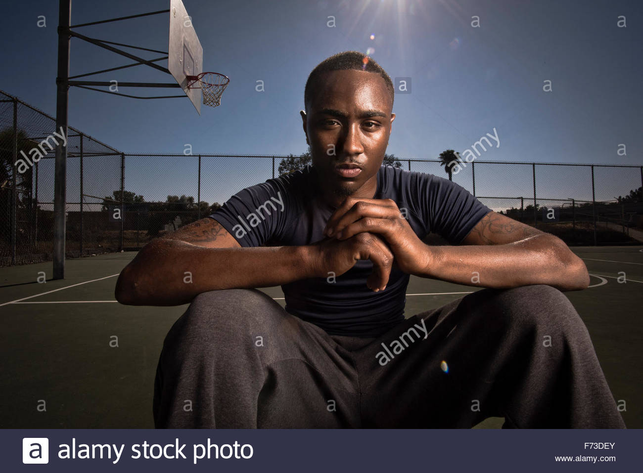 A basketball player rests on the court after a game. - Stock Image