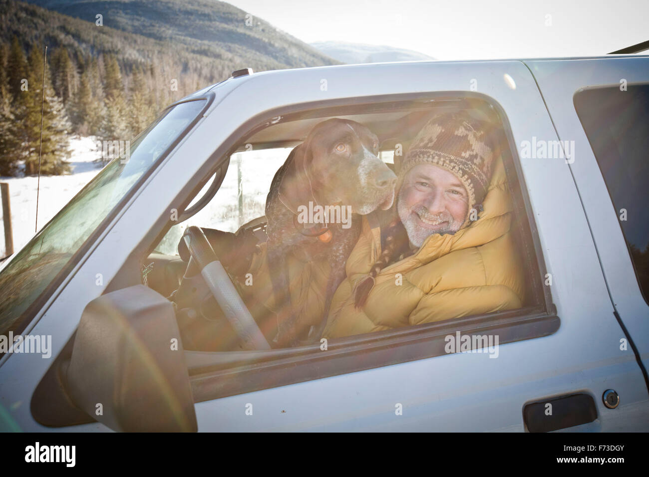 Portrait of a man and his dog in a truck. - Stock Image