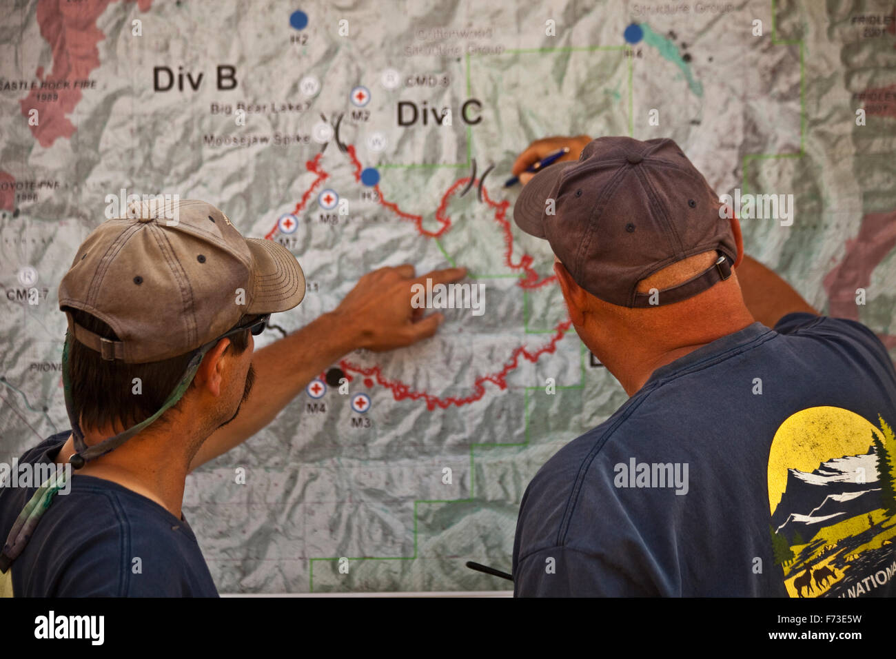 Two wild land firefighters look at a map to decide the day's plan of attack. - Stock Image