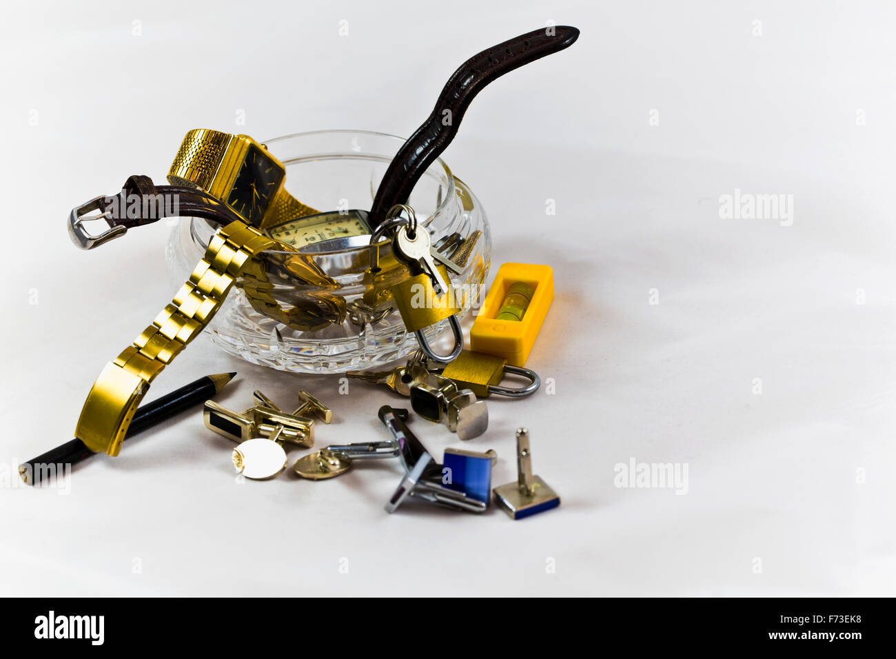 Crystal jar full of mens watches small padlocks and keys, cuff-links, small spirit level - Stock Image