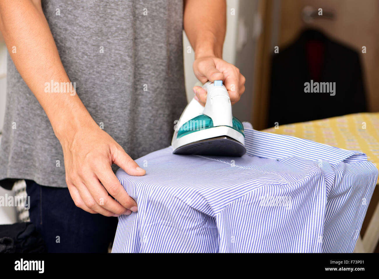 closeup of a young man ironing a striped shirt with an electric iron - Stock Image