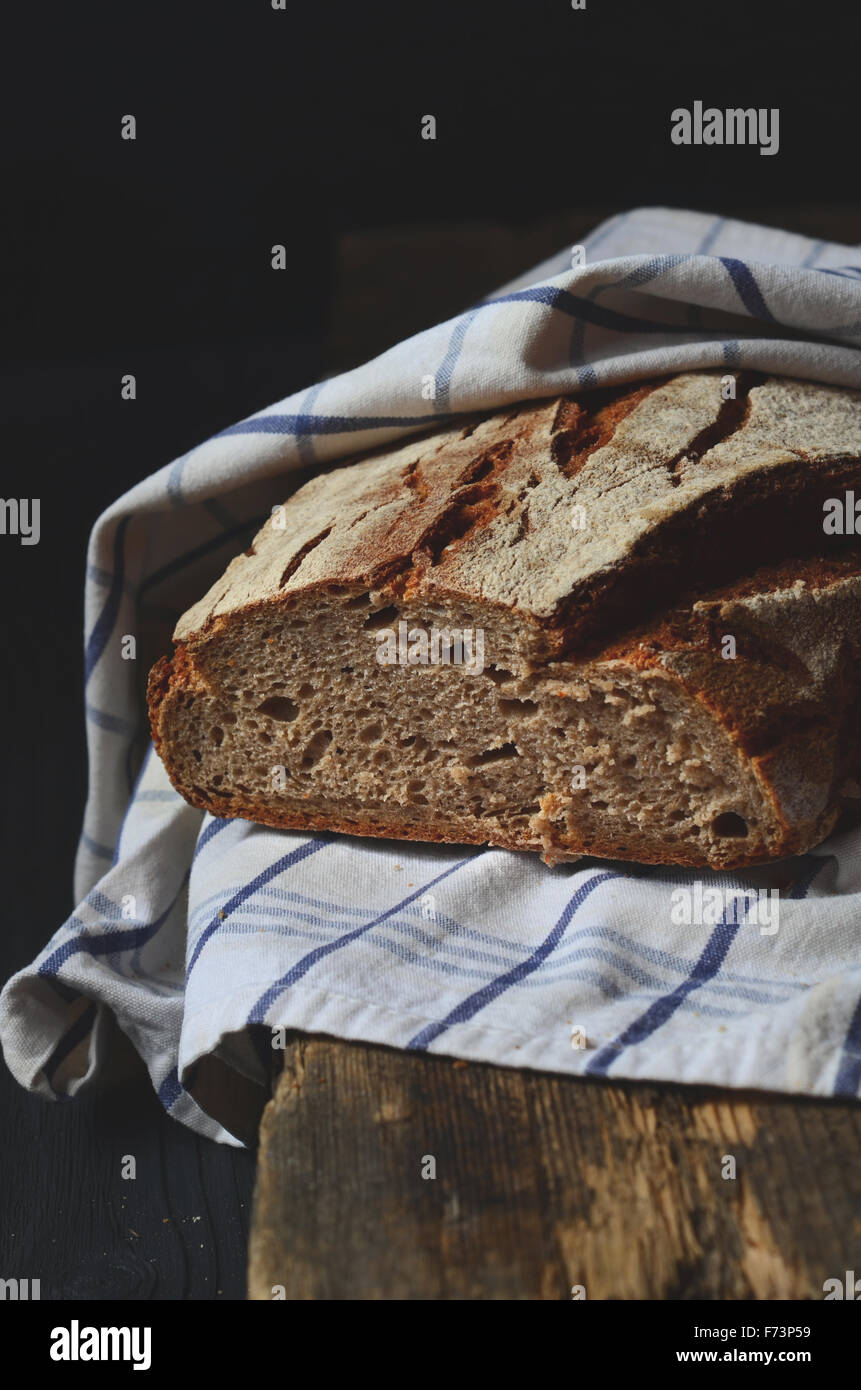 Freshly baked traditional homemade bread on wooden table - Stock Image