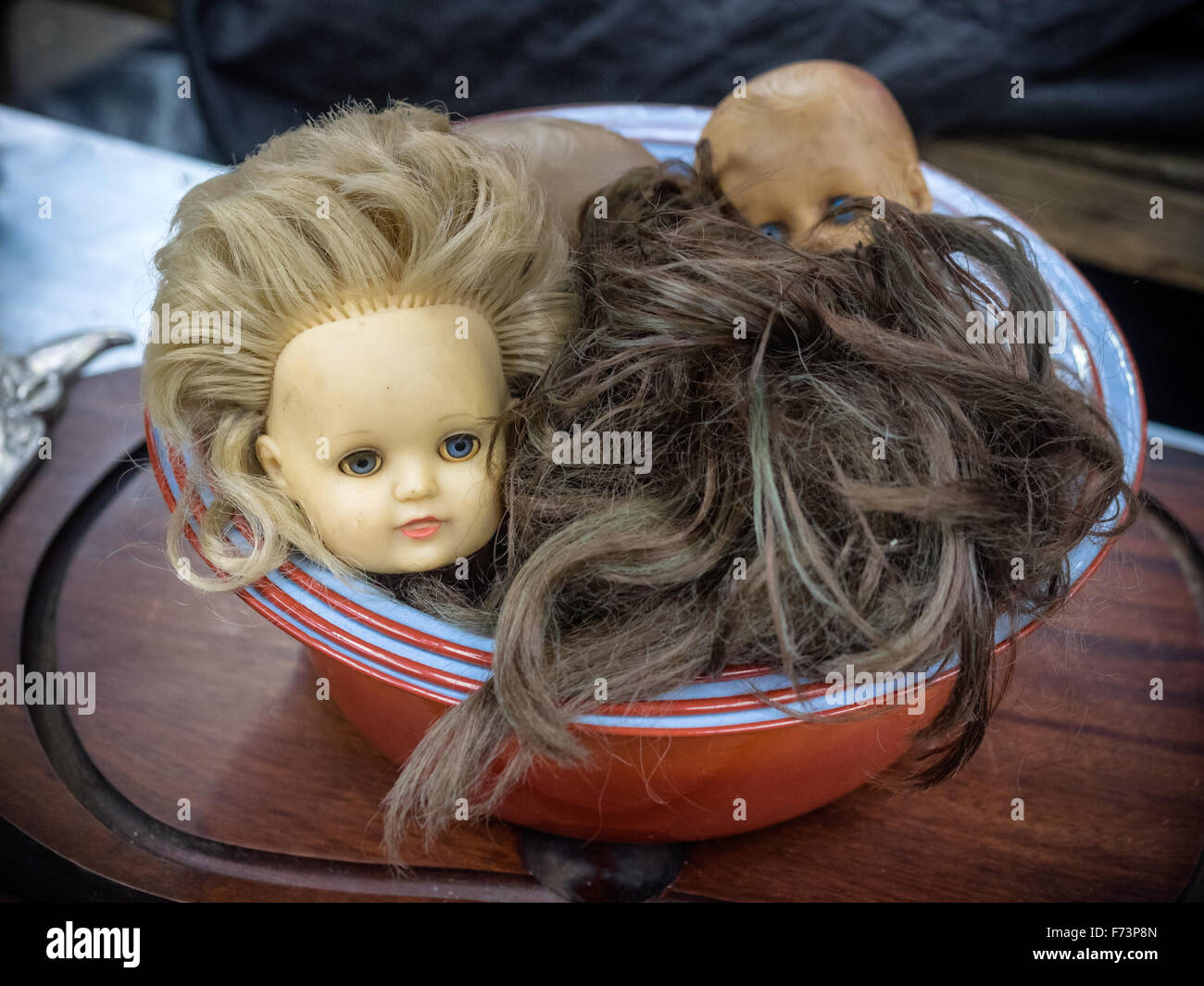 Antique doll heads in a big bunch, some of them are broken - Stock Image