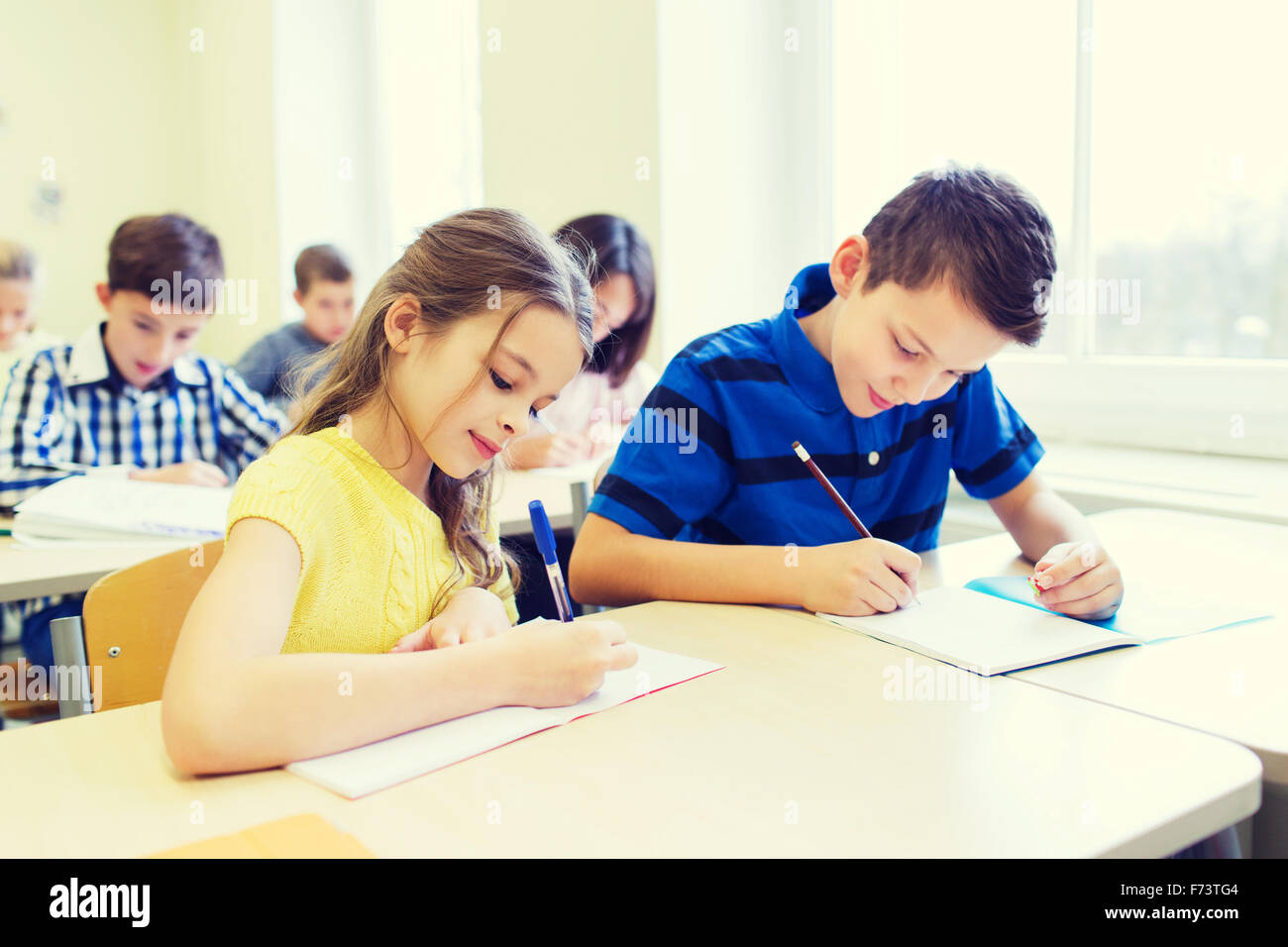 group of school kids writing test in classroom stock photo: 90439556