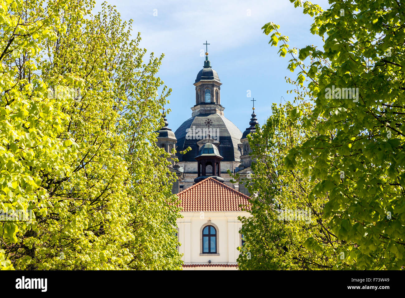 Baroque monastery of Pazaislis in Kaunas, Lithuania seen through green trees - Stock Image