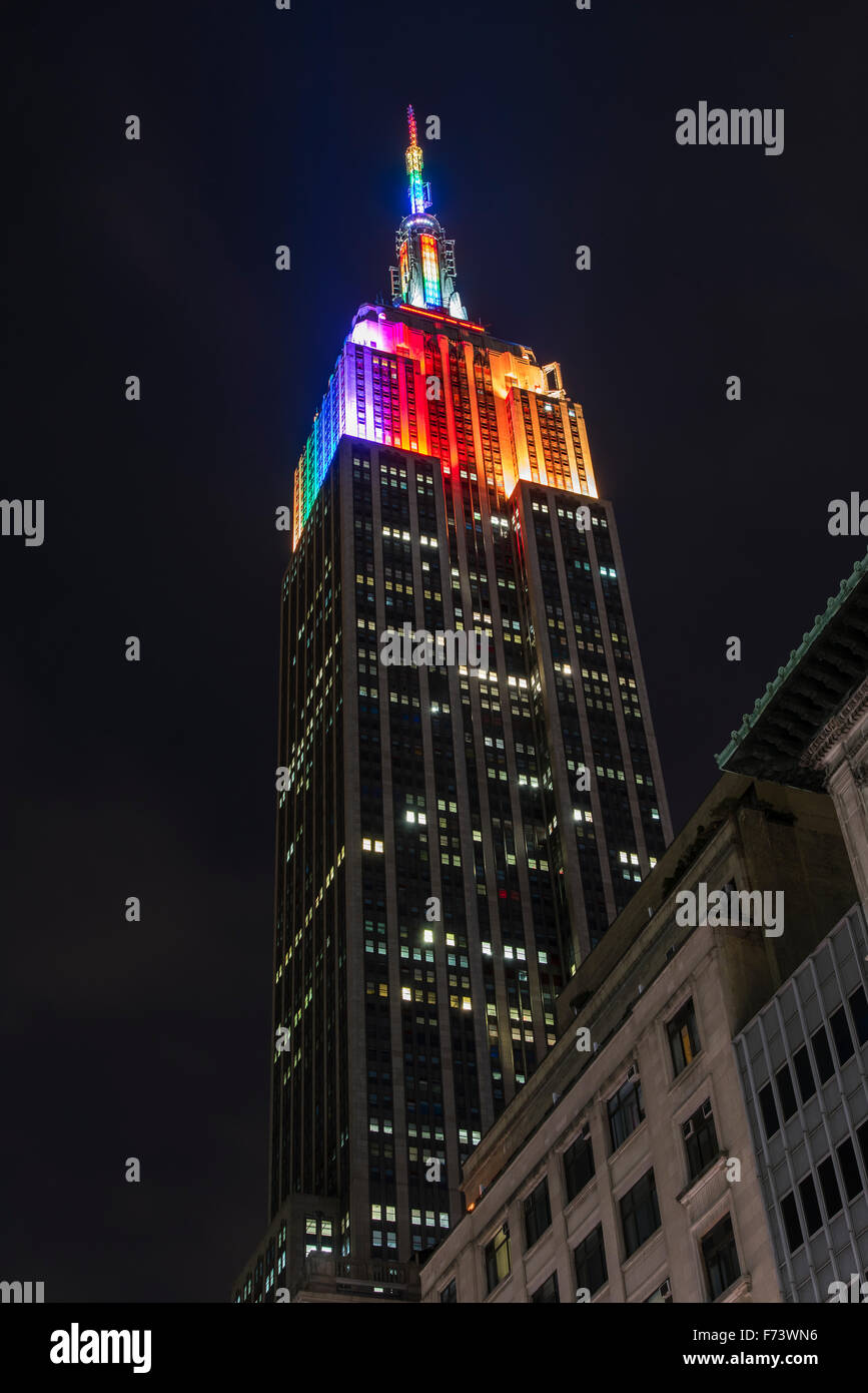 Night low angle view of the Empire State Building with rainbow colors, Manhattan, New York, USA - Stock Image