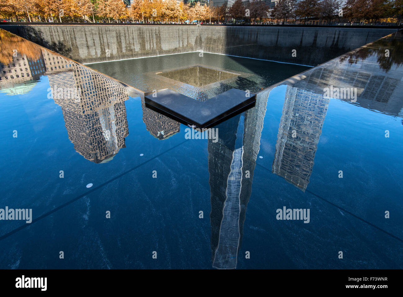 Southern Pool of National September 11 Memorial & Museum with One World Trade Center reflected, Lower Manhattan, Stock Photo
