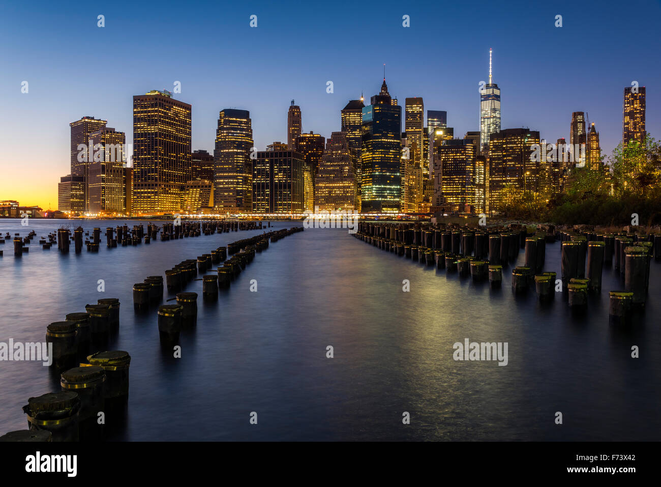 Lower Manhattan skyline at dusk from Brooklyn Bridge Park, Brooklyn, New York, USA - Stock Image